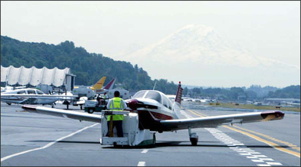 A ground-crew member moves a plane to the flight line at Boeing Field. The arrival of Southwest Airlines would require costly improvements.