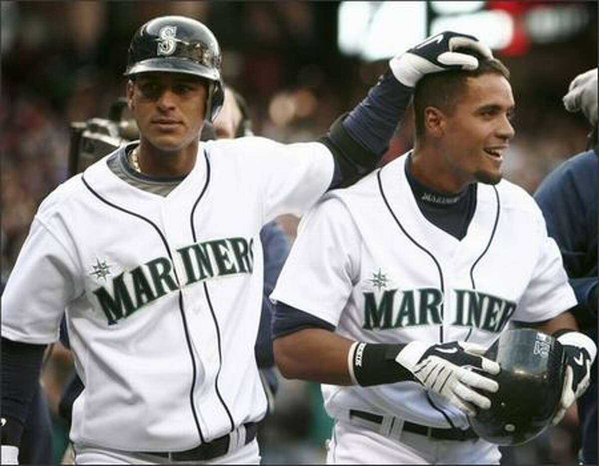 Ronny Cedeno, left, congratulates teammate Franklin Gutierrez after he scored the winning run against the Los Angeles Angels in this April 14 photo. Both players are part of the newer half of the Mariners roster, which seems to be getting stronger as the MLB draft deadline approaches.