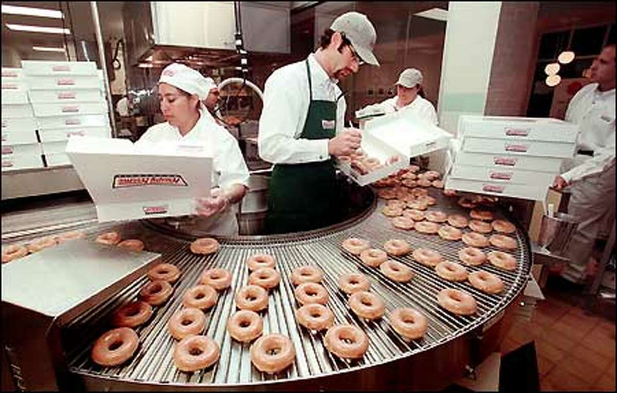 Workers at the Krispy Kreme Doughnuts store in Issaquah prepare the company's signature glazed doughnuts for the crowds at the store's grand opening last October.