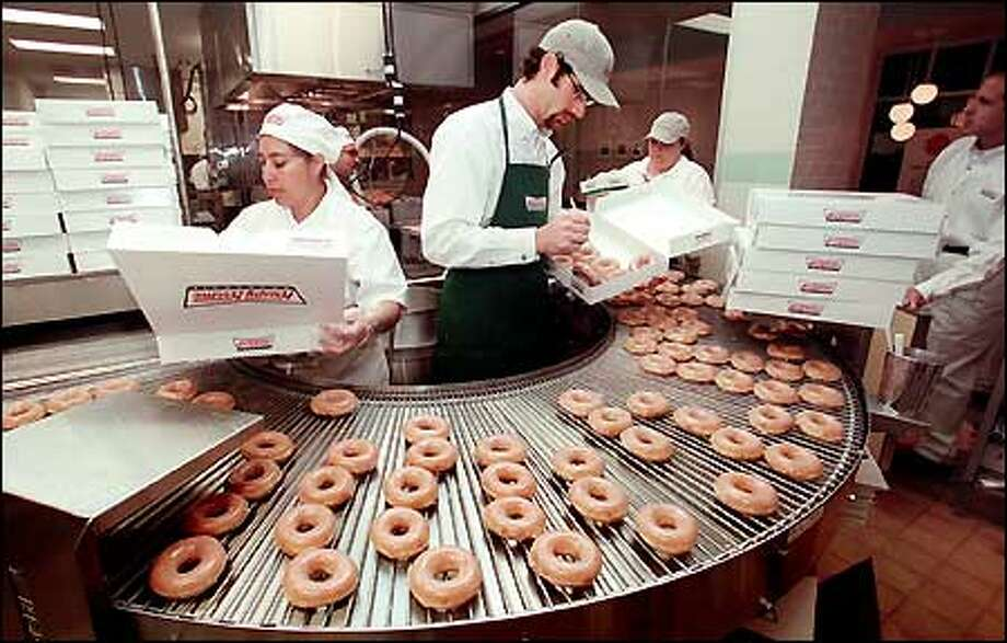 Workers at the Krispy Kreme Doughnuts store in Issaquah prepare the company's signature glazed doughnuts for the crowds at the store's grand opening last October. Photo: Seattle Post-Intelligencer / Seattle Post-Intelligencer