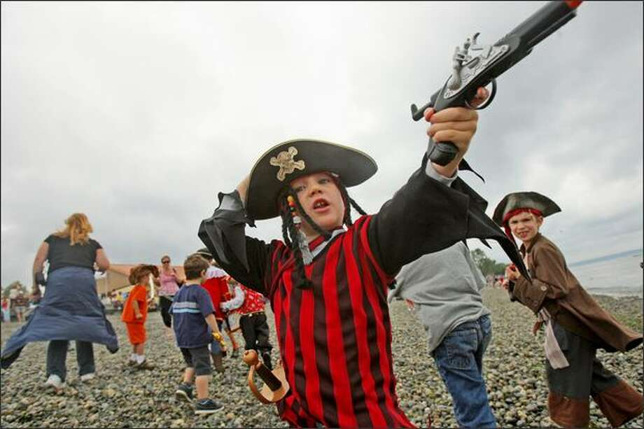 "Gavin Dallas, 3, of Sammamish, ""the Jack Sparrow of the Dallas',"" according to grandfather Bob Sheehan of Mercer Island, takes aim at off-shore pirate ships while waiting for the Seafair Pirates to arrive. Photo: Mike Kane, Seattle Post-Intelligencer / Seattle Post-Intelligencer"