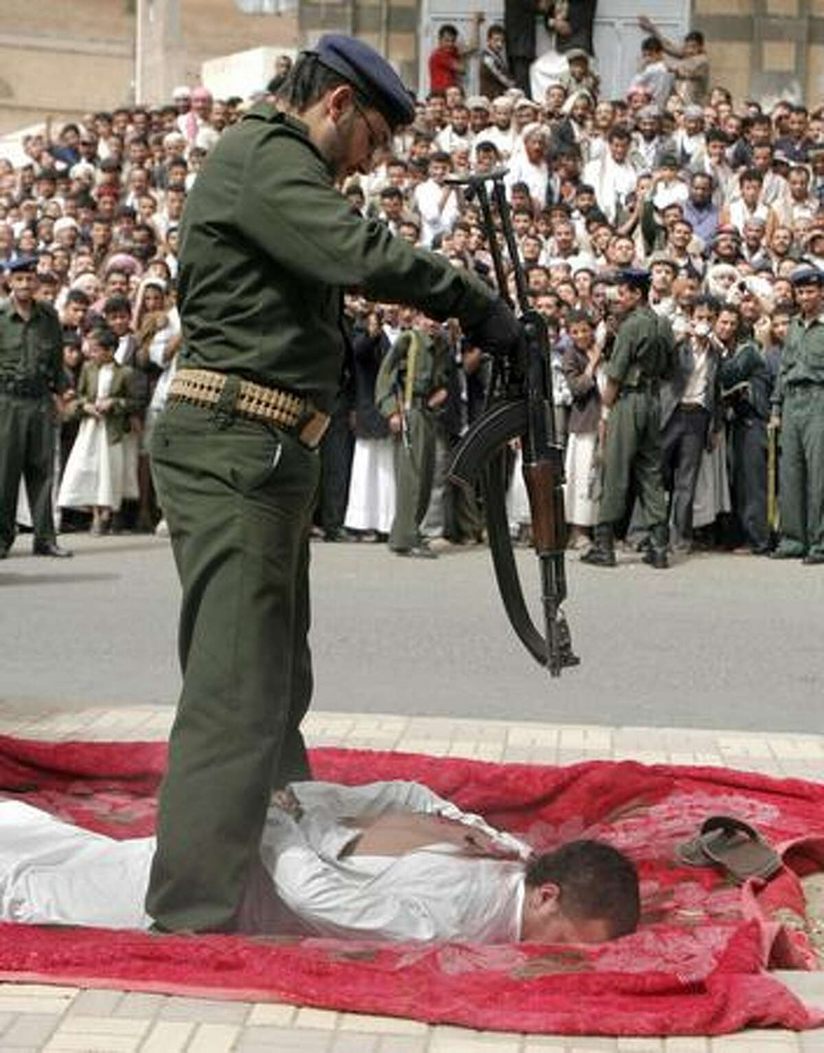 Yemenis gather to watch a soldier execute a man, lying face down on a large piece of red cloth, his hands bound behind him, in front of the central prison in San'a. According to Yemen's news agency, the man was sentenced to death for raping and killing an 11-year-old boy who came to his shop for a haircut. He confessed at trial to the crimes, as well as to cutting his body to pieces before dumping it outside San'a. (AP photo)