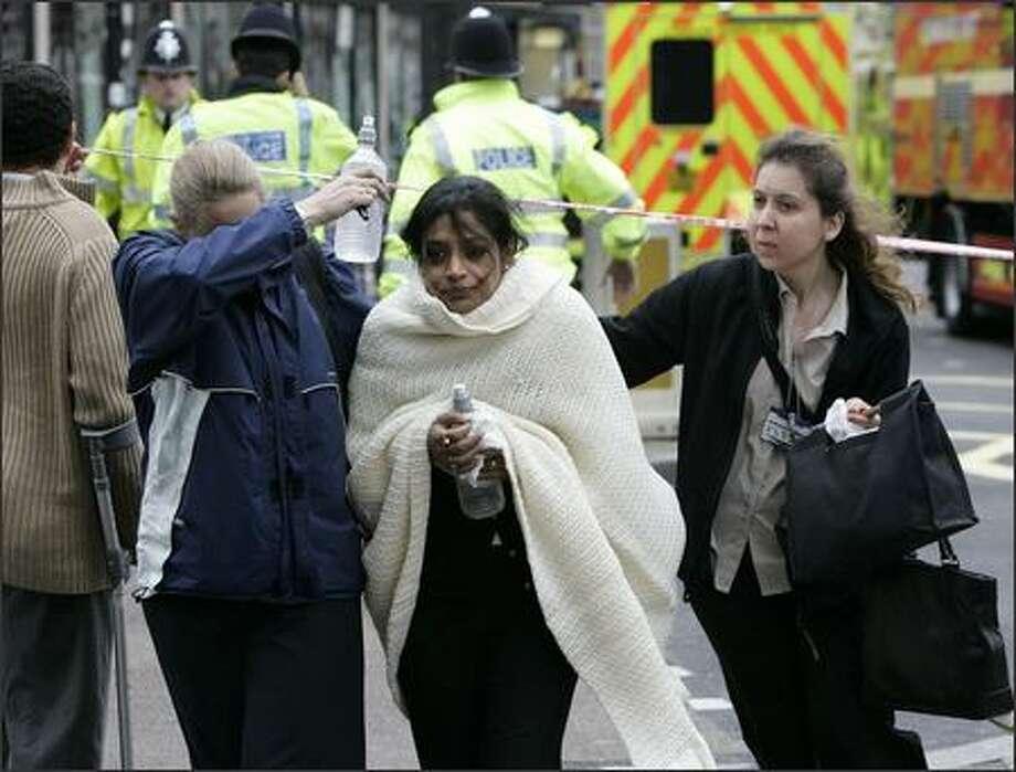 Walking wounded leave Edgware Road tube station in London. (AP Photo/Edmond Terakopian/PA) Photo: Associated Press / Associated Press