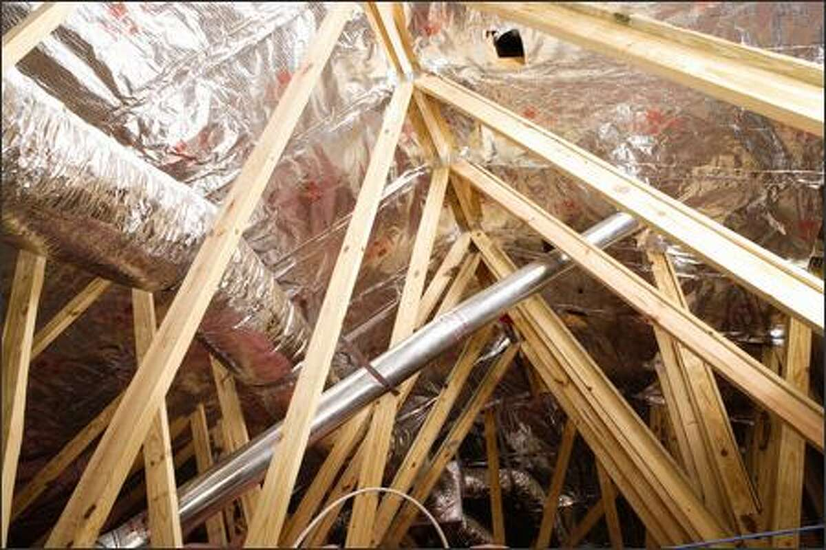 Nylon mesh-reinforced attic foil is stapled under the roof rafters. (FI-FOIL)