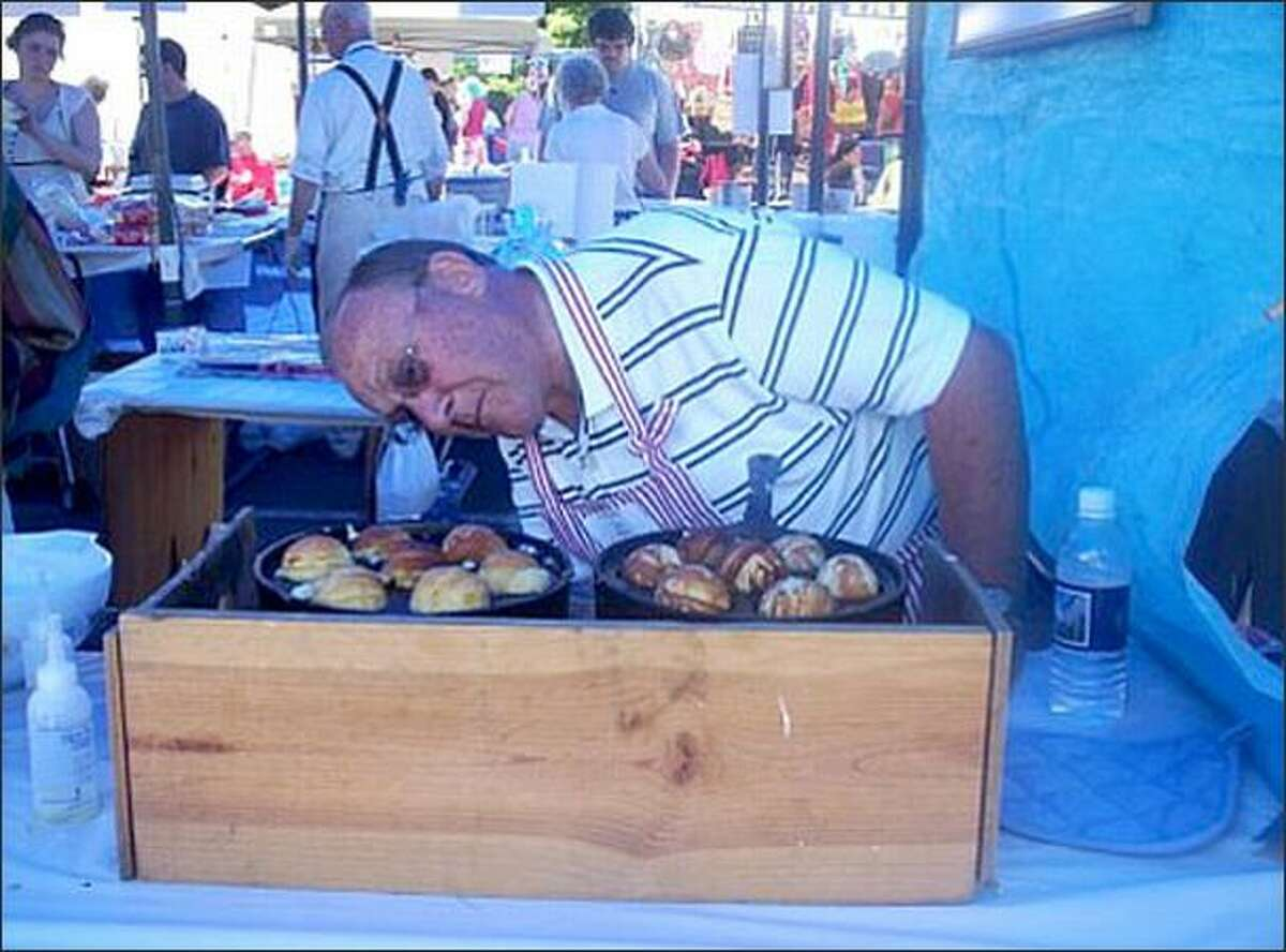 Tivoli voluneer Paul Jensen keeps a close watch on the aebleskivers he cooked for the Nordic Heritage Museum's Viking Days festival Saturday. Aebleskiver, which means apple slice, is a traditional ball-shaped Danish pancake.