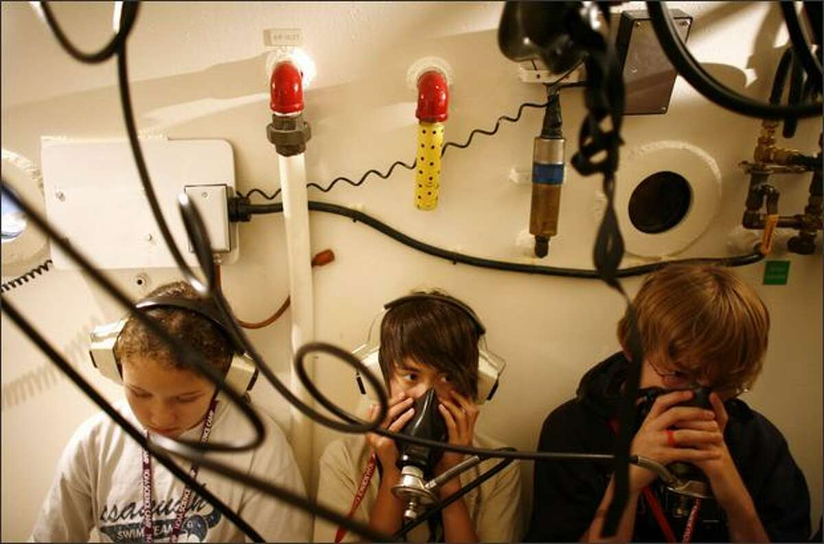 Noah Genatossio, 12, and Brock Breed, 13, learn about the hyperbaric chamber Monday at NOAA's Sand Point dive facility.