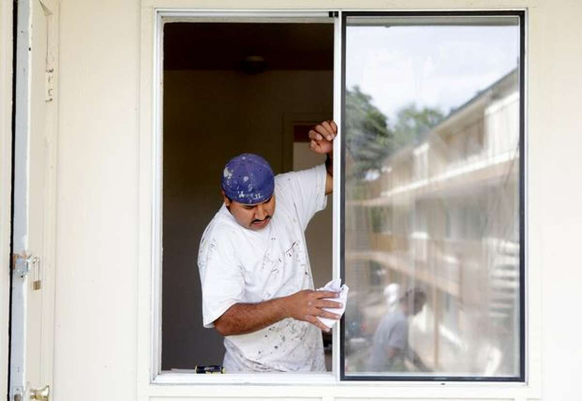 Workers wash windows, paint, and remove brush at the Creston Park Apartments.