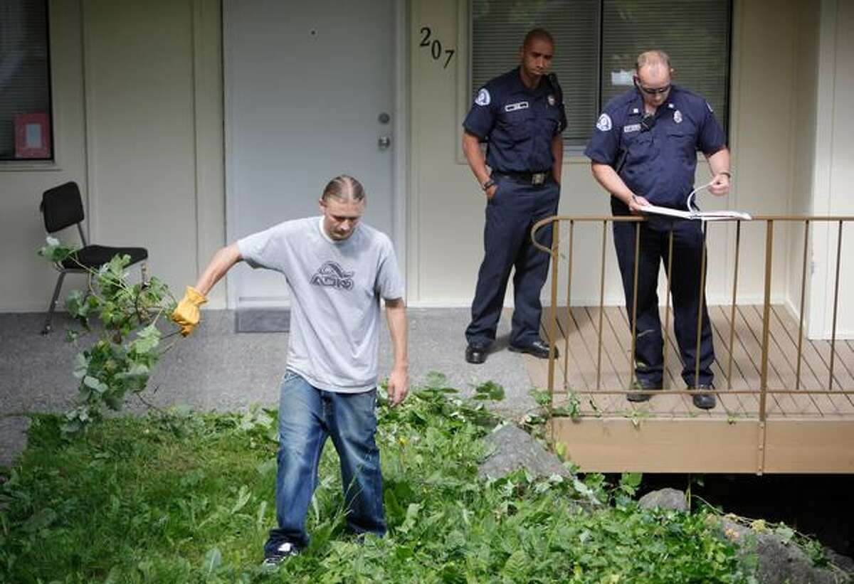 Seattle Fire Department firefighters perform an inspection of the Creston Park Apartments while a worker removes overgrown weeds.
