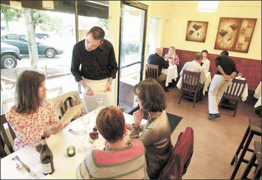 Server Daniel Jarrett discusses the evening's menu at Dandelion, a new American bistro-style restaurant in Ballard. Photo: Paul Joseph Brown, Seattle Post-Intelligencer / Seattle Post-Intelligencer