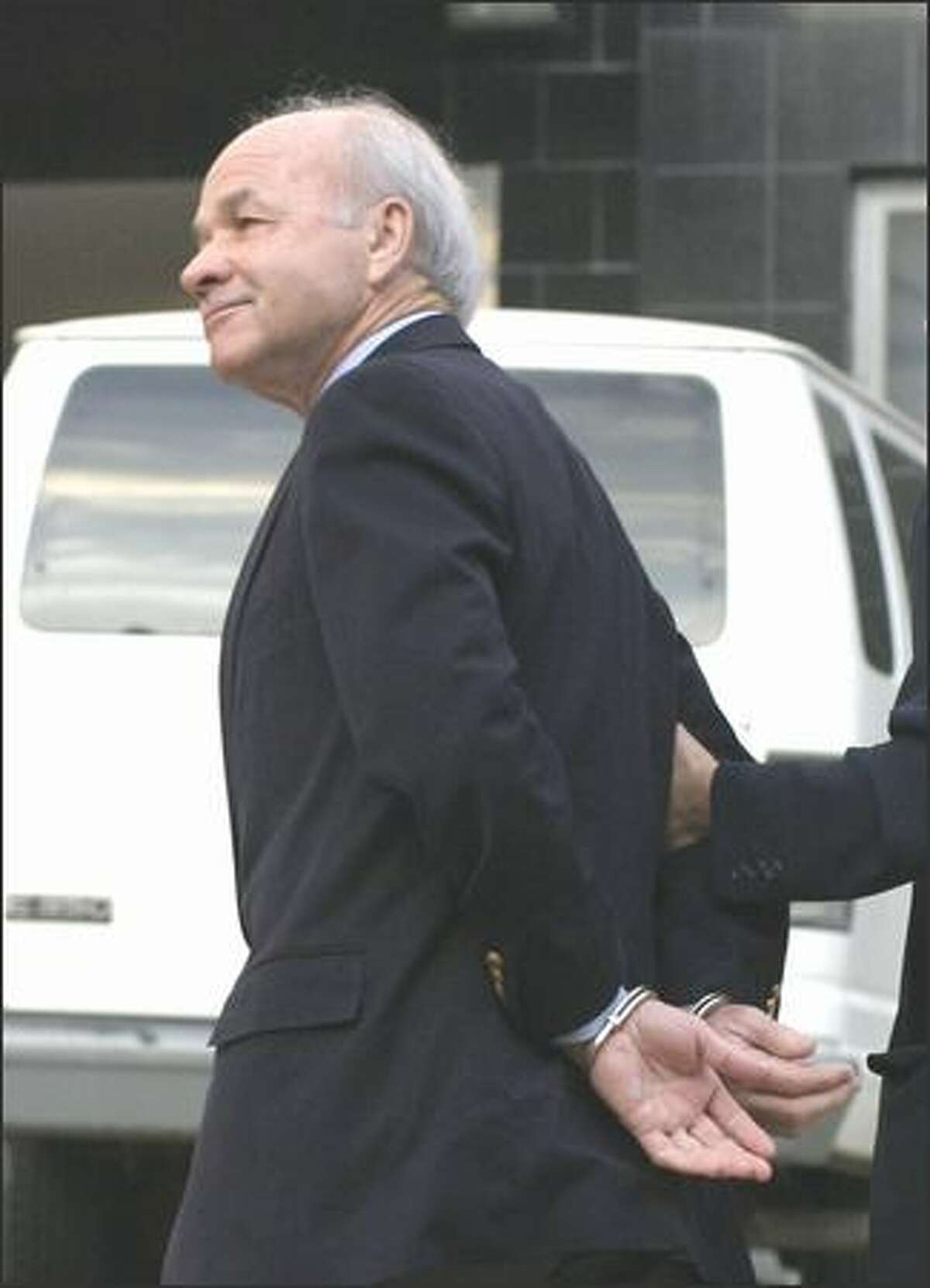 Former Enron Chief Executive Officer Kenneth Lay is led into federal court in Houston yesterday.