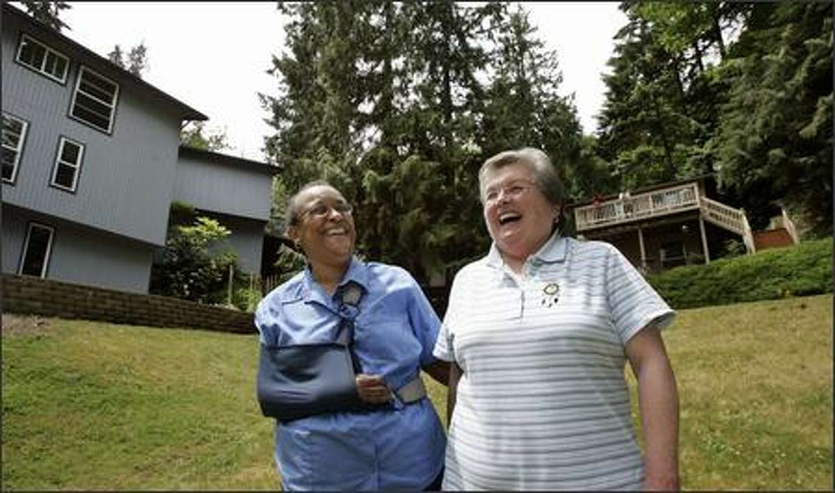 Teresa Jones, left, and her partner, Nancy Nystrom, stand in the yard of the property they are developing as a cohousing community for retired women. Their project will cater to lesbians.