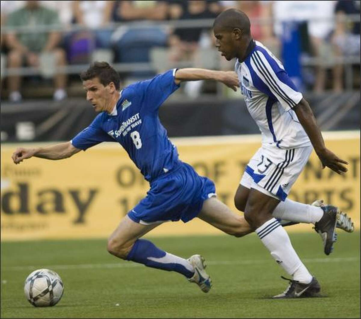 Seattle Sounders forward Sebastien Le Toux, left, falls to the Qwest Field turf under pressure from Rauwshan McKenzie of the Kansas City Wizards during their Lamar Hunt U.S. Open Cup quarterfinal match Tuesday night.