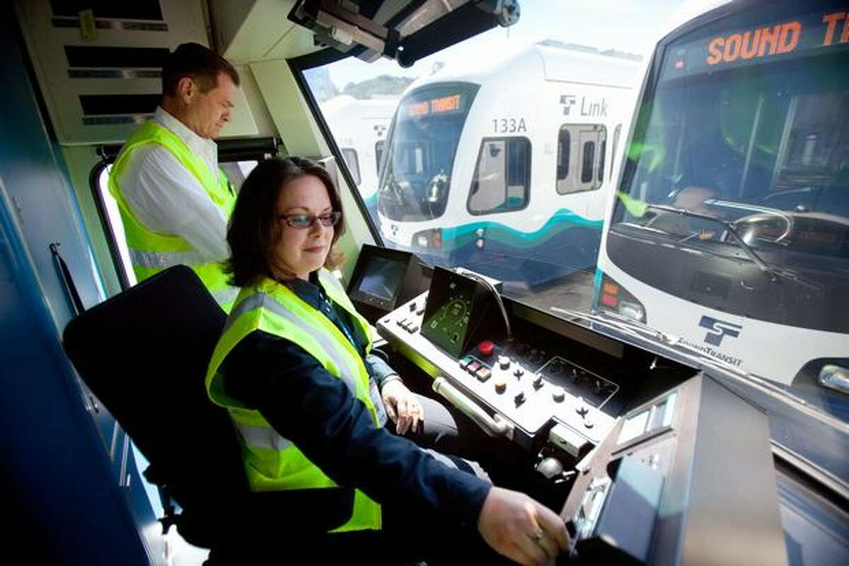 Sound Transit light rail operators John Helm, left, and Annette James show a new train at the operations and maintenance center. Helm and James were both recruited from the ranks of Sound Transit bus drivers to operate the new light rail trains.