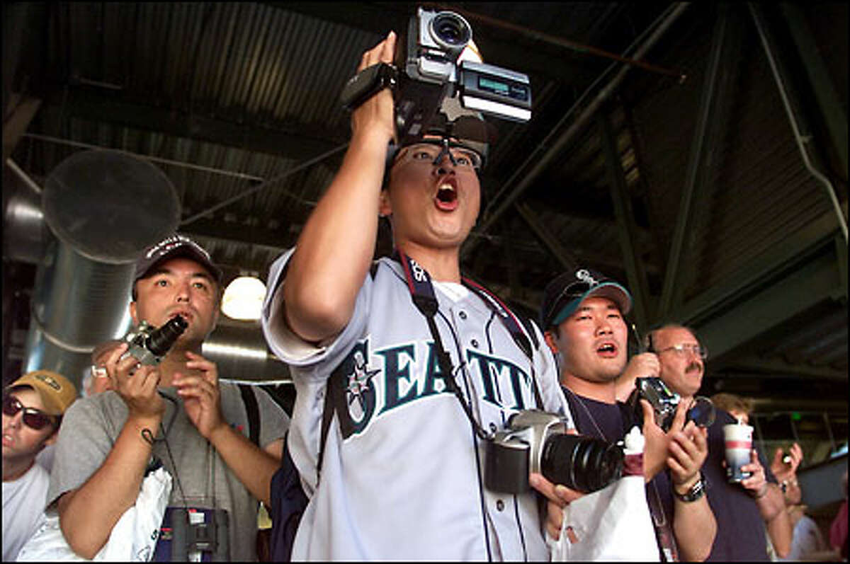 Toru Shimazui, center, flanked by Akinobu Kadotani, left, and Ryu Tania, cheer Mariners' star Ichiro Suzuki during batting practice. The three are part of a group that came from Japan for the All-Star Game.