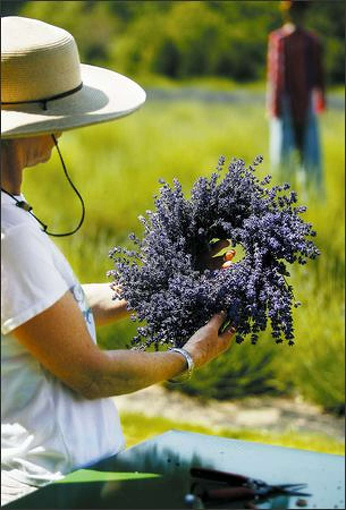 Chris Shuman inspects a lavender wreath she and Linda Hill were making at Cyndi Johnson's Fox Farm.