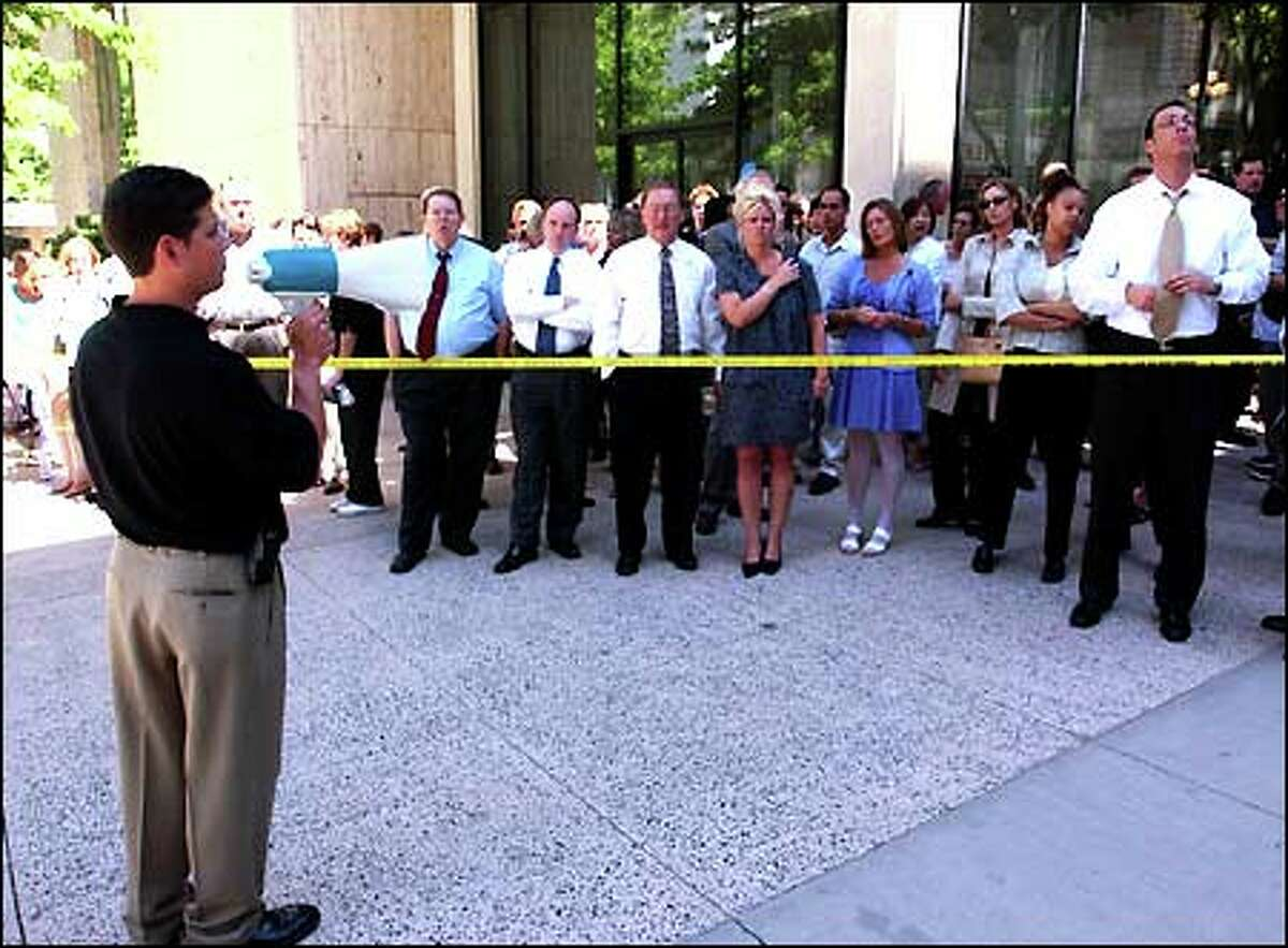 John Miller, Financial Center building manager, instructs people evacuated from the building after a smoke bomb was set off on the 23rd floor. The building is located at Fourth avenue and University street.