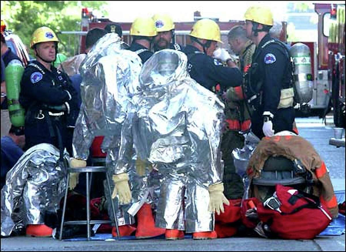 Specialists from the Seattle Fire Department suit up before they go into the Financial Center building after a smoke bomb caused workers to evacuate.