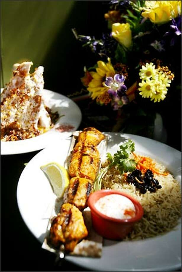 Bamiyan's menu includes, in the foreground, Murgh kebab (marinated, grilled white-meat chicken) and Quruti (Afghan bread coated in yogurt-garlic sauce), rear left. Photo: Scott Eklund, Seattle Post-Intelligencer / Seattle Post-Intelligencer