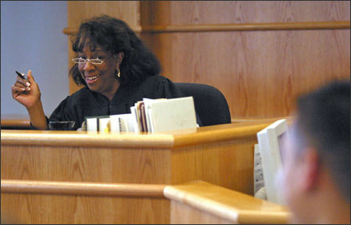 Judge Patricia Clark talks to a boy about his new job and progress at school during King County juvenile court proceedings.