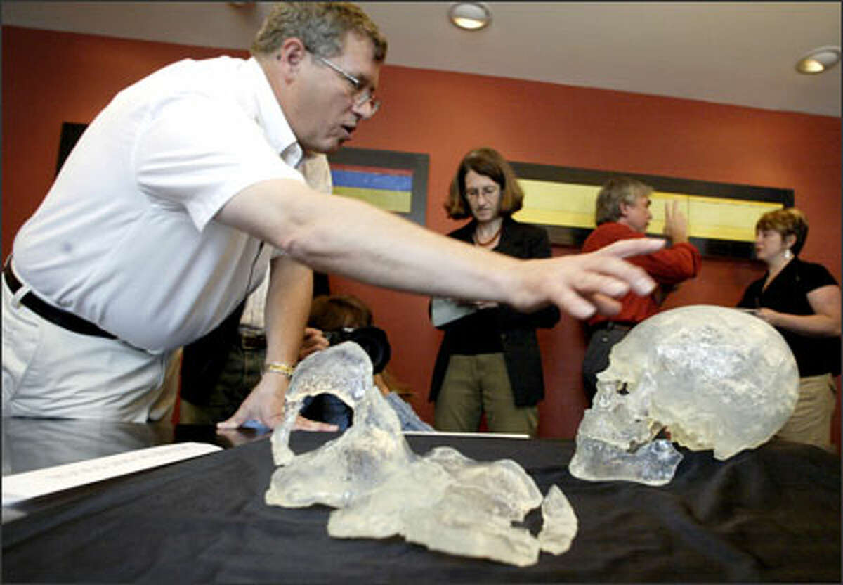 Douglas Owsley uses replicas of Kennewick Man's skull and pelvis bone to explain the 11-person scientific team's study of the 9,300-year-old bones.