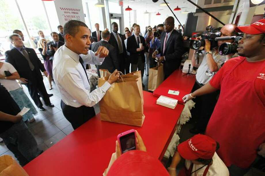 In this May 29, 2009 file photo, President Barack Obama orders a hamburger at the Five Guys Burgers and Fries in Washington. With a drive-through seemingly on every corner, you might think the burger market long ago reached saturation. But the fastest-growing restaurant chain in America last year was Five Guys, which specializes in double-pattied behemoths. (AP Photo/Gerald Herbert, File) Photo: Associated Press / Associated Press