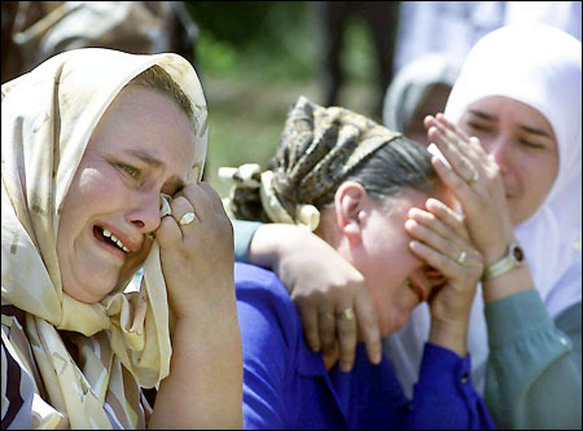 Weeping Bosnian women console one another yesterday on the sixth anniversary of the systematic massacre of 8,000 Muslim men and boys by Serbian forces in the village of Potocari, near Srebrenica, in July 1995. Thousands of tearful Muslims attended the laying of a marble memorial stone for the victims.