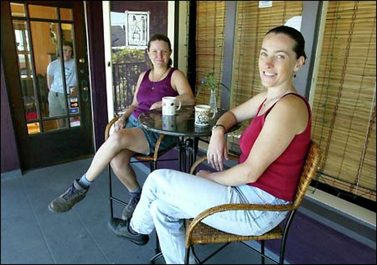 Roo McKenna, center, and Connie Stone, owners of the Wild Mountain Cafe, sit on the porch of their restaurant. Standing in the door is Stone's 11-year-old daughter, Chenoa Orme-Stone.