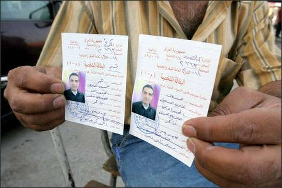 An Iraqi outside his Baghdad shop displays ID cards he made for the same person -- one with a Sunni name and one with a Shiite name.