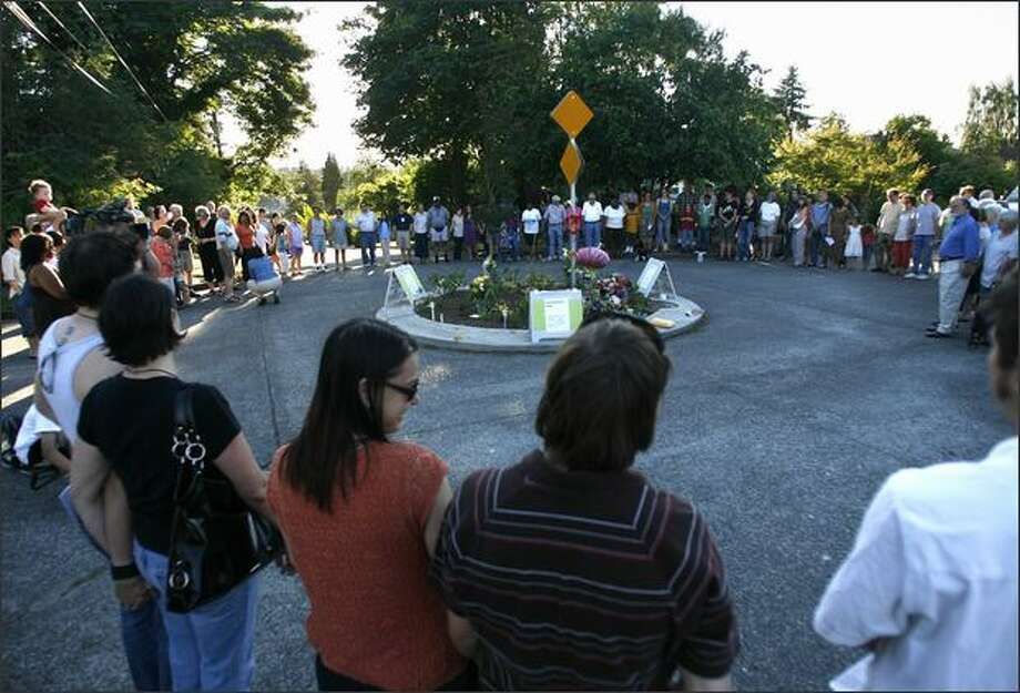 "Neighbors of James Paroline gather in a circle and hold hands at a candlelight vigil Friday. ""We will not be the same,"" one neighbor said. ""We will only be better because we resolved in ourselves to stand and do the right thing."" Paroline died after an altercation near the traffic circle he was tending Wednesday night. Photo: Kristine Paulsen, Seattle Post-Intelligencer / Seattle Post-Intelligencer"