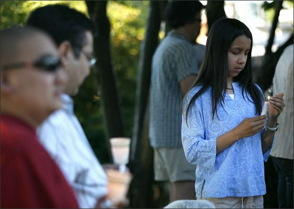 Neighbor Marissa Dominguec carefully tends her candle at a vigil Friday evening for James Paroline.