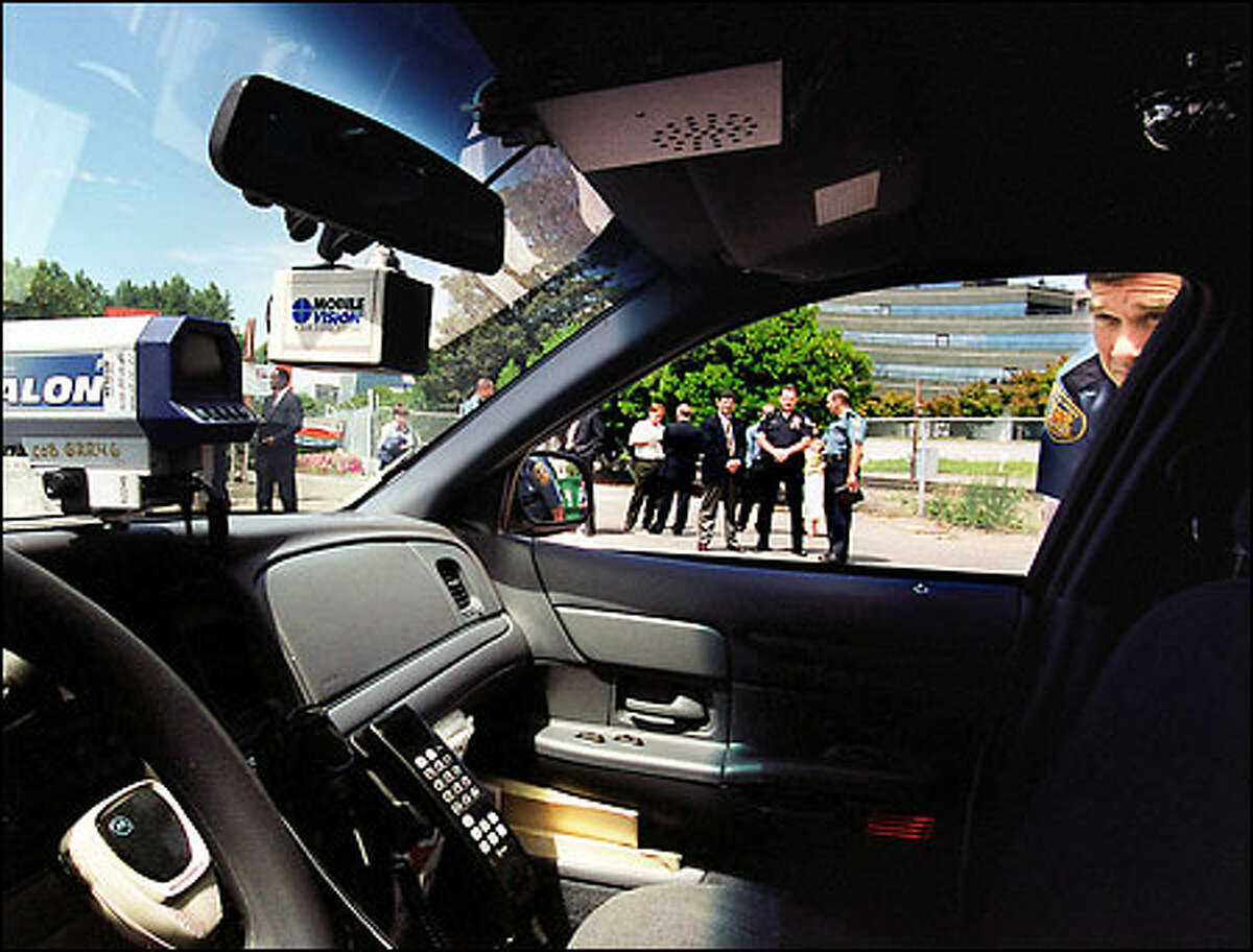 Seattle Police Chief Gil Kerlikowske peers into a Bellevue patrol car that has a video camera installed, visible below the rearview mirror. (The device at left is a radar detector.)