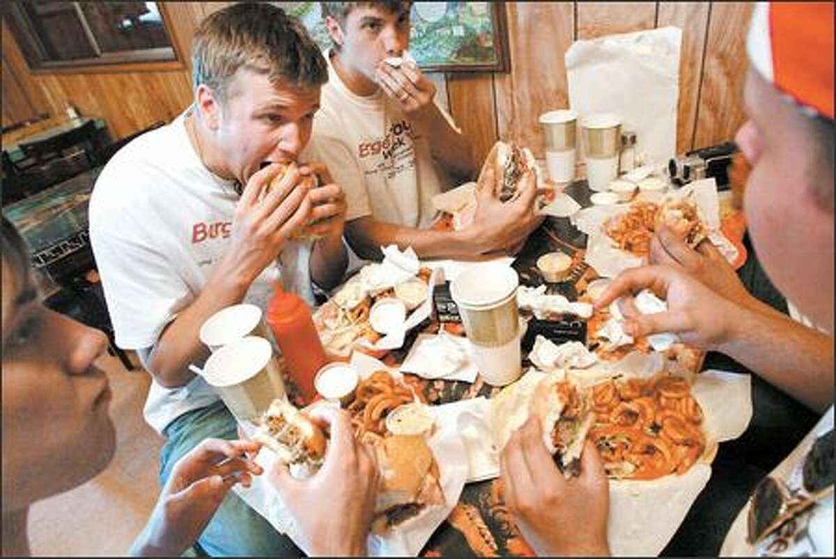 At the Chuck Wagon Drive-In in Mount Vernon, from left, Alex Bennett, Kyle Buckingham and Tyson Williams wolf down the Bar Six, which sported a full pound of beef.
