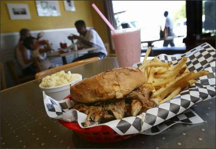 The barbecue pulled-pork sandwich, here with sides of fries and mac and cheese and a strawberry milkshake, is the best thing on the menu. Photo: Andy Rogers, Seattle Post-Intelligencer / Seattle Post-Intelligencer