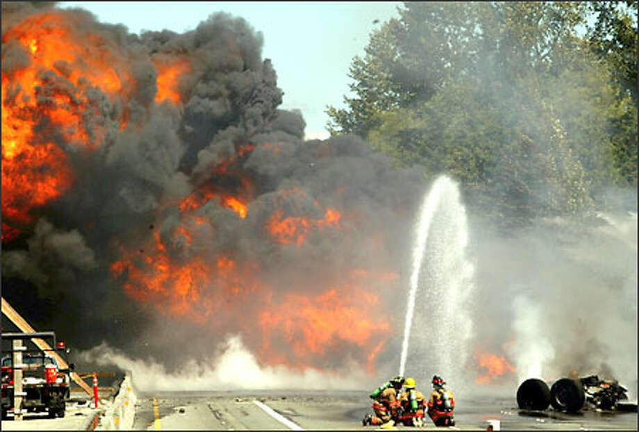 Lynnwood firefighters train a hose on flames and smoke pouring out of a burning tanker truck on an I-5 overpass in Lynnwood Saturday. The freeway was closed for hours. Photo: Grant M. Haller, Seattle Post-Intelligencer / Seattle Post-Intelligencer