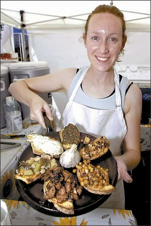 "At the Ballard Farmers Market, Jennifer Mcllvaine holds an iron skillet full of grilled toasts called ""bruschettinas,"" topped with fresh ingredients from neighboring booths. Photo: Jim Bryant, Seattle Post-Intelligencer / Seattle Post-Intelligencer"