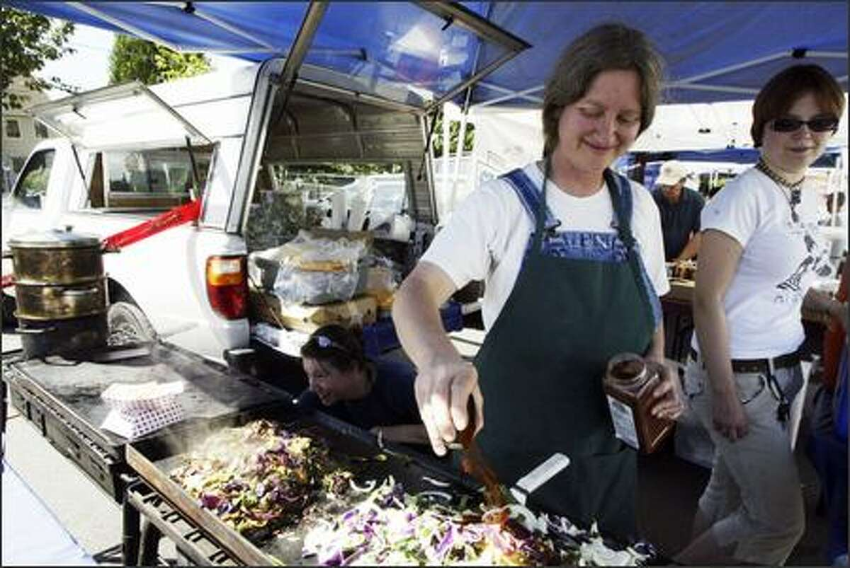 At Columbia City's market, Devra Gartenstein, owner of Patty Pan Grill, shakes paprika onto cooking vegetables for quesadillas as co-worker Lucy Weiland watches and Lynn Flory, left, minds the grill.