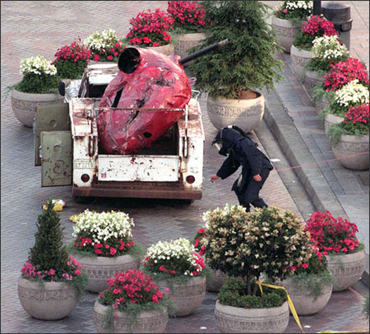 A Seattle Police bomb squad member cautiously inspects the truck Sprinkle abandoned in Westlake Park in downtown Seattle in July 1996.