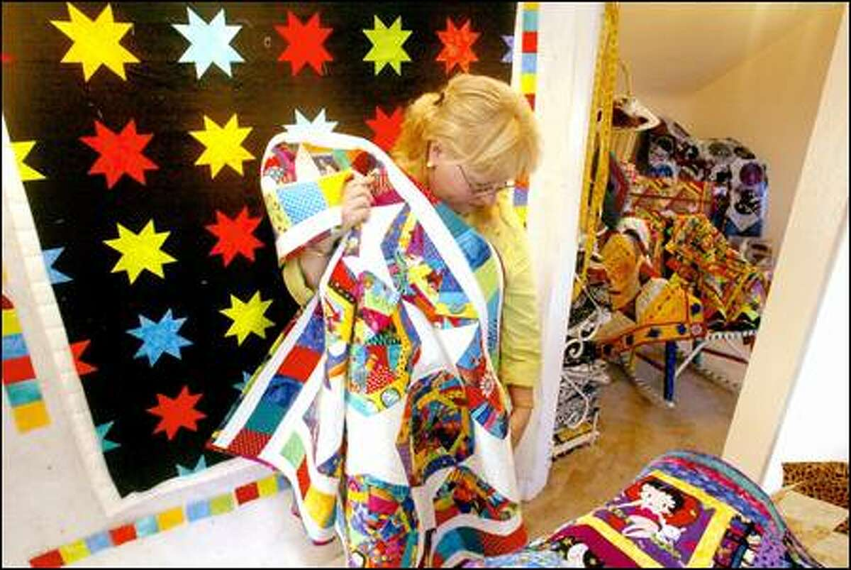 Julia Lebert unfurls some of her quilts, which she makes and gives to women and children at New Beginnings.