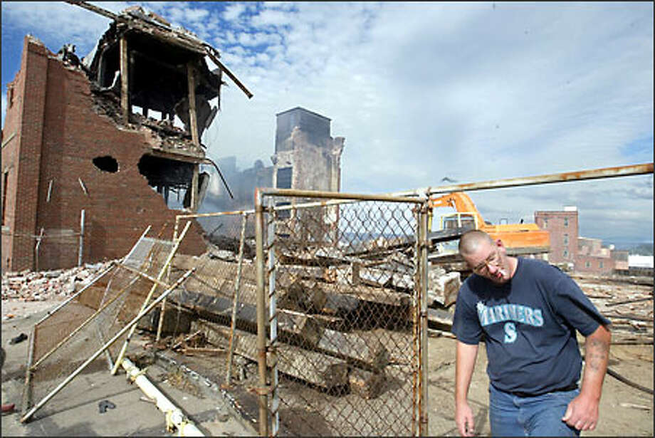 The still smoldering remains of Alpine Cold Storage in Tacoma, which was destroyed by fire last week and is being demolished, is drawing its share of looky-loos, including Steve Garcia, who stepped inside the fence yesterday to check out the ruins. Photo: Scott Eklund, Seattle Post-Intelligencer / Seattle Post-Intelligencer