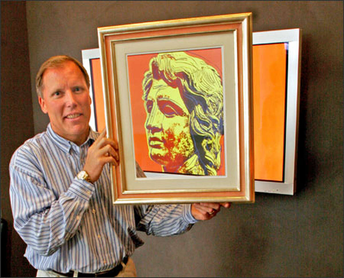 GalleryPlayer CEO Craig Husa displays a piece by Andy Warhol, one of the artists whose work the company makes available for display on high definition TVs in homes.