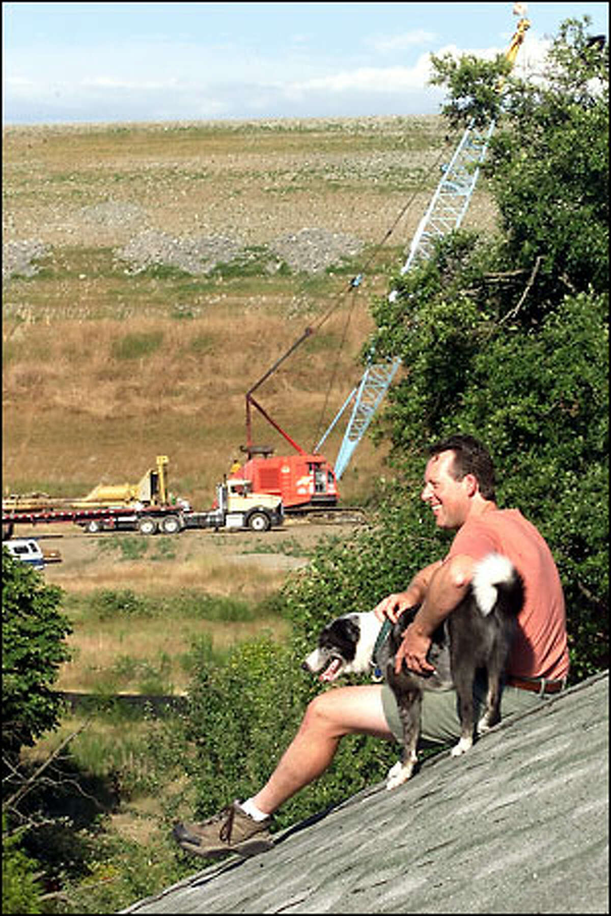 Work on Sea-Tac Airport's third runway goes on near the home Lyle Wammer shares with his dog Oi off Des Moines Memorial Drive. So far, 3 million cubic yards of fill have been trucked in -- and the Port of Seattle still has 13.5 million cubic yards to go.