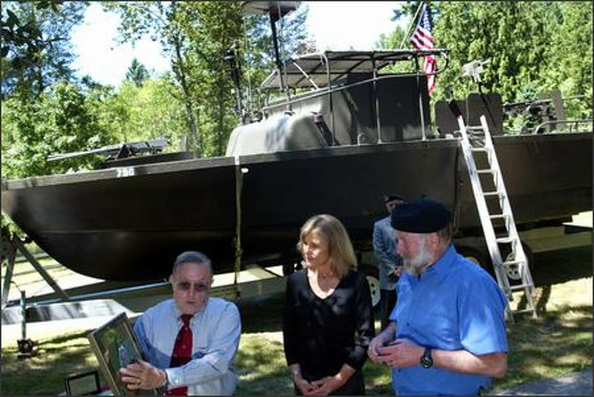A replica of the riverboat Rubin Binder served on sits in the background as a plaque honoring Binder is presented to his wife, Kris, at her home in Snohomish on Sunday. Making the presentation is Fred McDavitt, left, commander of Binder's riverboat section.
