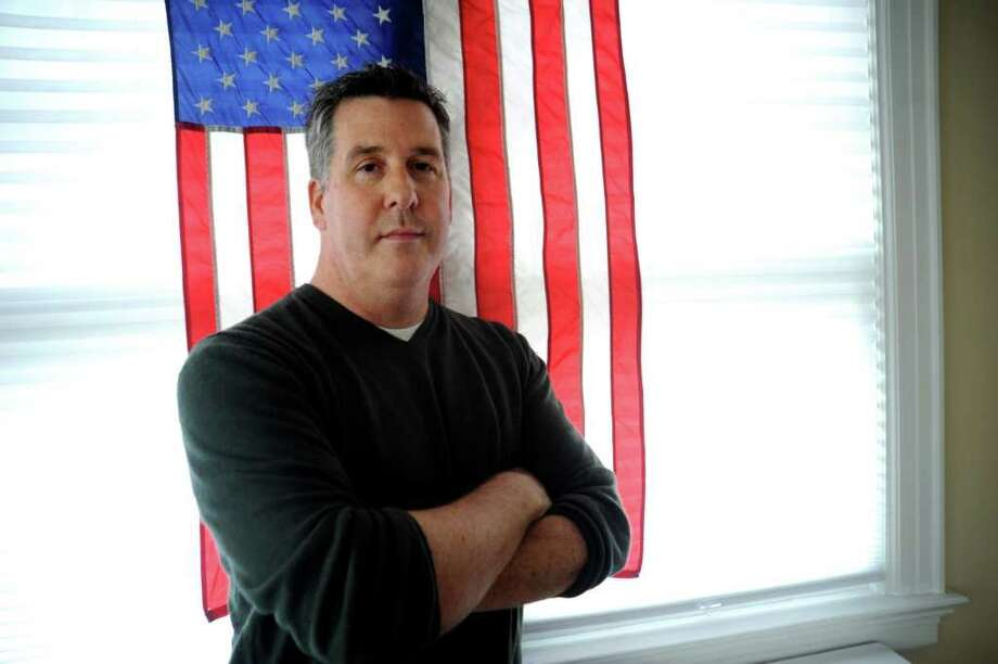 Christopher Hughes, who served with the U.S. Marines during the Gulf War, stands with an American flag at home on Tuesday, April 5, 2011. Photo: Helen Neafsey / Greenwich Time