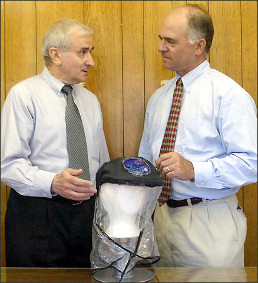 Boris Altshuler, left, and James Reynolds, president of CR Clean Air Technologies, received a patent for their baseball cap-style gas mask. Their goal was to create a lightweight, portable gas mask that could be used by the average American in the event of a chemical attack. Photo: New York Times / New York Times