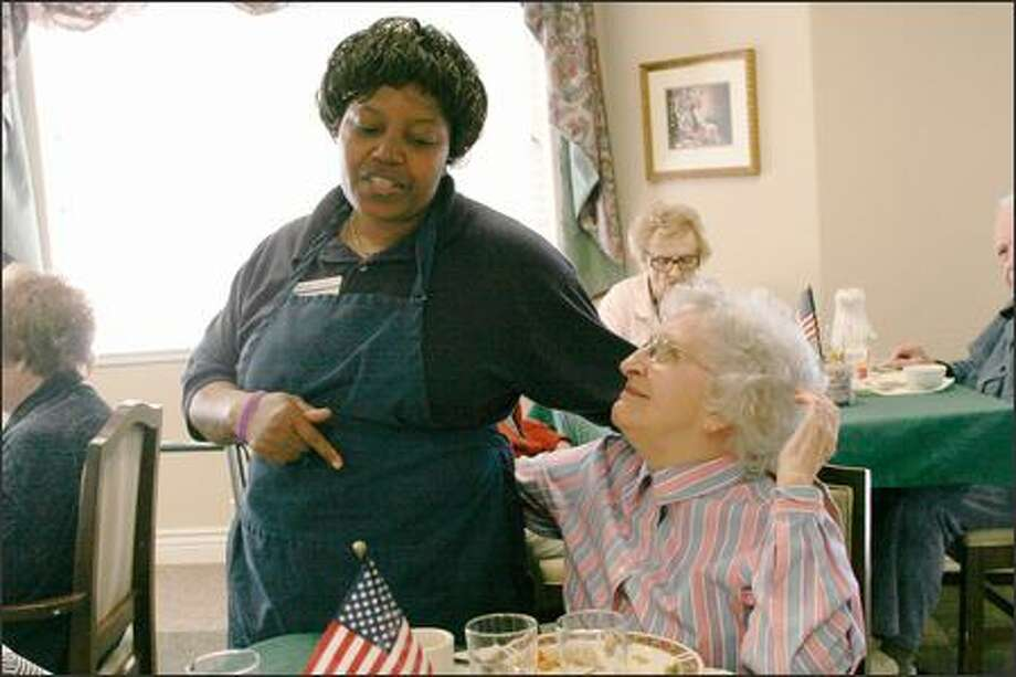 Ami Na Ta, an assistant at Aegis Senior Living, an independent living community in Shoreline, jokes with resident Lorna Sierk during a recent dinner. Photo: Niki Desautels, Seattle Post-Intelligencer / Seattle Post-Intelligencer