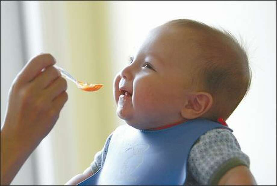 Aleister Zin Alfstad, 4 months old, is ready to start tasting Sprouts organic carrots fed to him by his mother, Elisa Hahn. Photo: Scott Eklund, Seattle Post-Intelligencer / Seattle Post-Intelligencer
