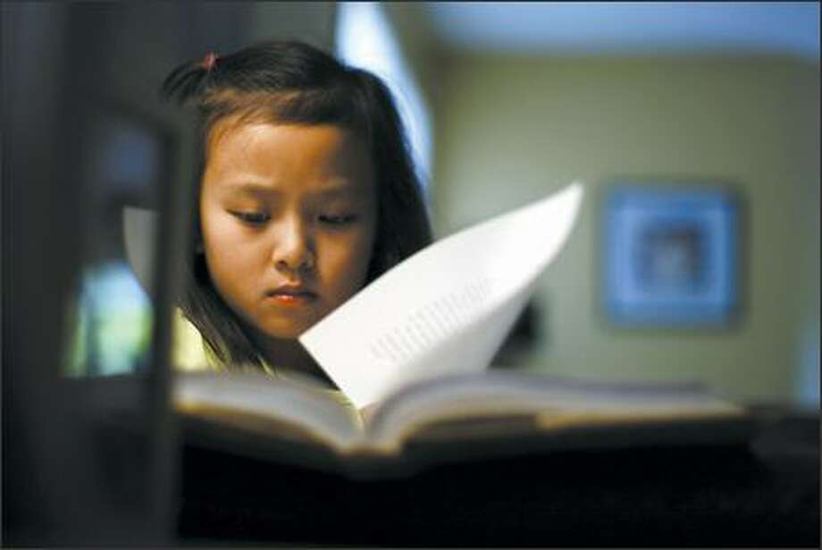 "Seven-year-old Jasmine Sun reads ""The Roald Dahl Treasury"" in her favorite reading spot in her Kirkland home Monday. Jasmine will have the latest Harry Potter book delivered at 12:01 a.m. Saturday for winning a writing contest that Amazon.com sponsored for the release. She says the Potter books are her favorites. Photo: Andy Rogers, Seattle Post-Intelligencer / Seattle Post-Intelligencer"