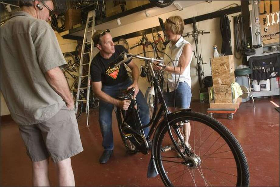 Dave Schmidt, center, co-owner of Dutch Bike Co. in Ballard, adjusts a bike seat for Marise Scott and Tom Dalbey. The sturdy imports offer an upright ride. Photo: Grant M. Haller, Seattle Post-Intelligencer / Seattle Post-Intelligencer