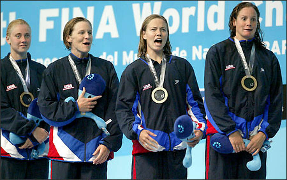 The victorious U.S. 4x100-meter freestyle women's relay team wearing their gold medals sing their national anthem  after winning the event at the 10th World Swimming Championships in Barcelona, Spain. From left are Rhi Jeffrey, Jenny Thompson, Natalie Coughlin and Lindsay Benko. Officials said for technical reasons the U.S. national anthem could not be played over the public address system. (AP Photo/Lionel Cironneau) Photo: Associated Press / Associated Press