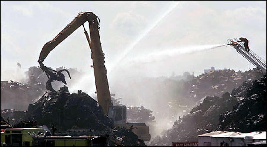 Tacoma firefighters continue to pour water on the smoldering piles of scrap near the city's Hylebos Waterway as small cranes pick through the debris. Photo: Mike Urban, Seattle Post-Intelligencer / Seattle Post-Intelligencer